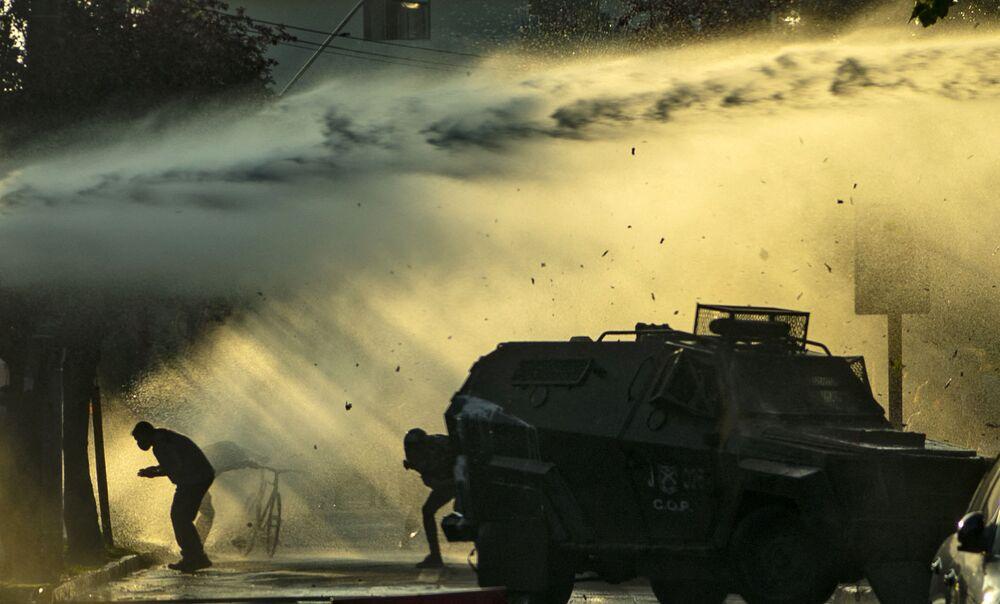 Artistas de rua enfrentam policiais durante protesto contra violência policial após assassinato de um artista de rua pela polícia local, Santiago, Chile, em 6 de fevereiro de 2021