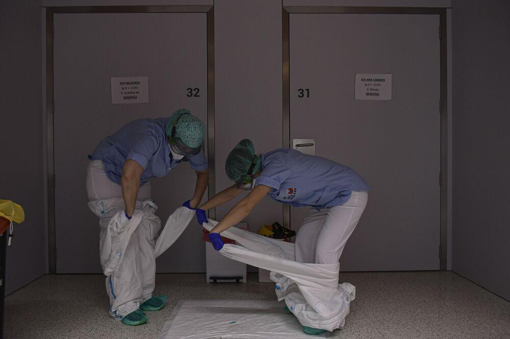 Funcionários tiram trajes de proteção no Hospital San Juan de Dios, Espanha, 8 de fevereiro de 2021