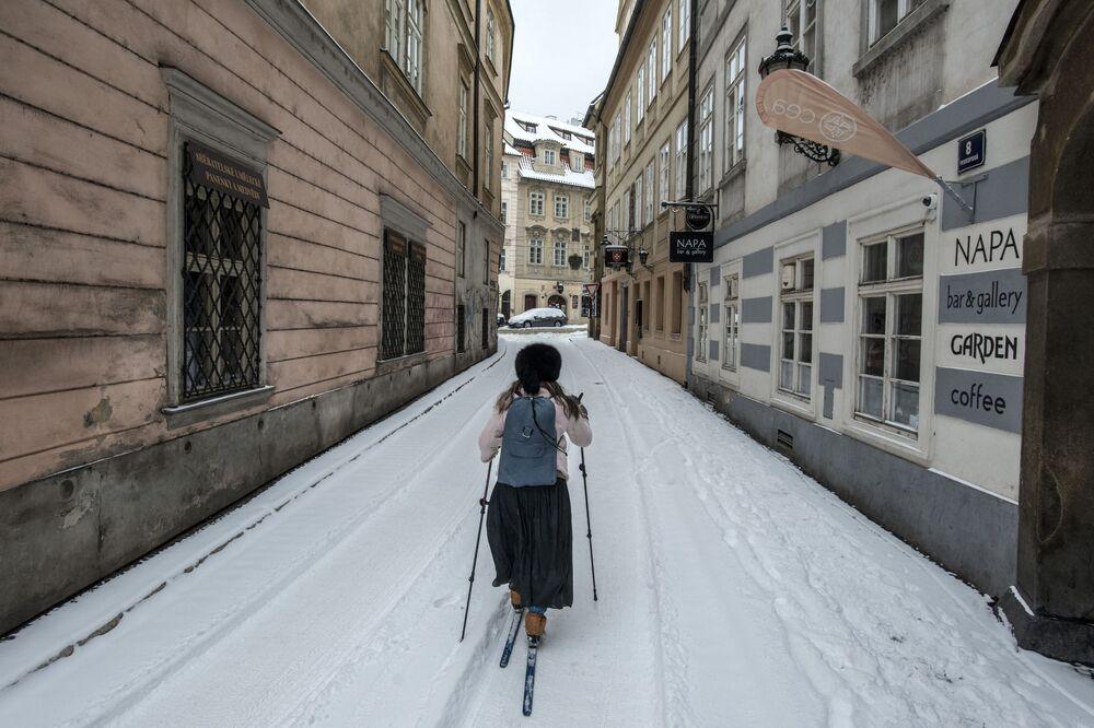 Mulher esquia após nevasca em rua de Praga, República Tcheca, 8 de fevereiro de 2021