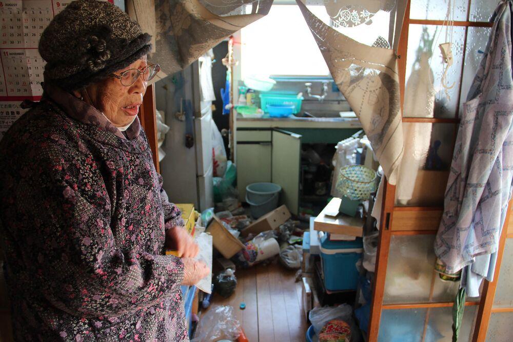 Mulher japonesa mostra utensílios de cozinha espalhados em sua casa na cidade de Soma, prefeitura de Fukushima