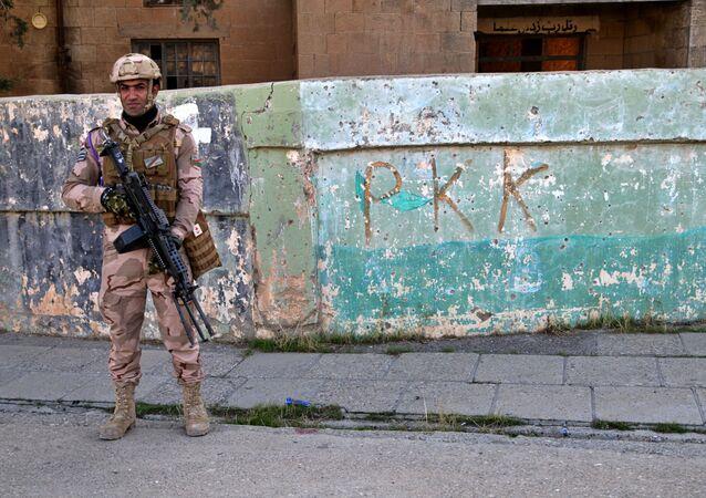Soldado iraquiano em frente ao muro com inscrição PKK