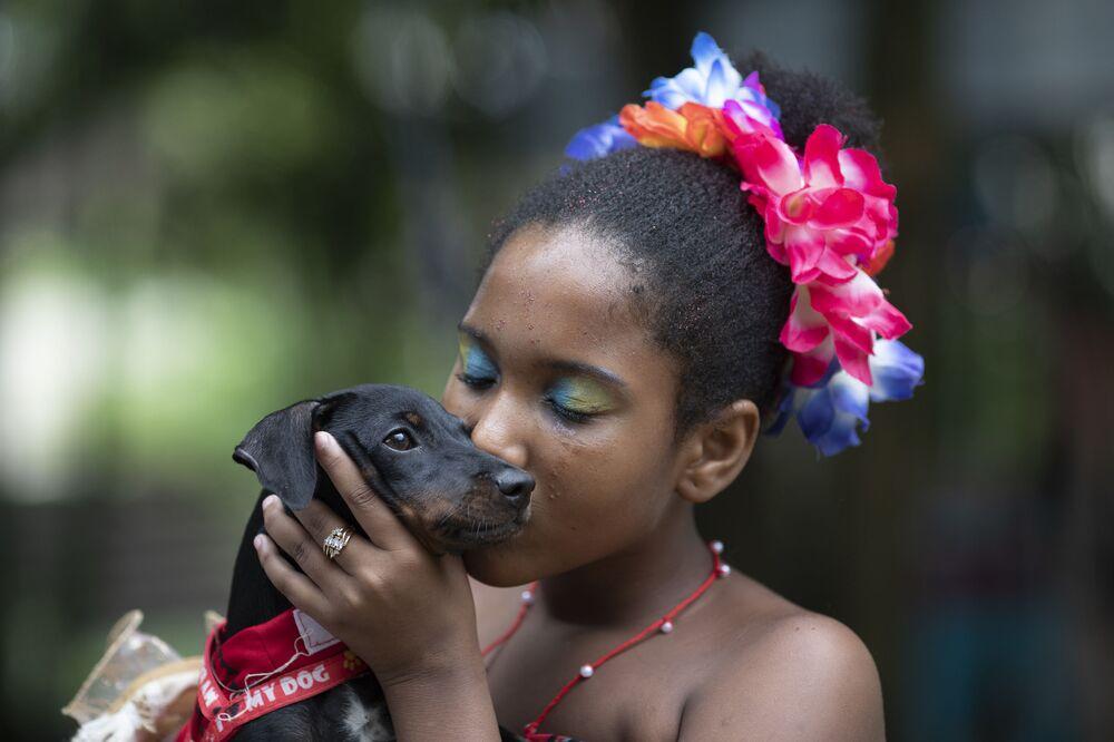 Sofia, de 11 anos de idade, beija seu cachorrinho durante o desfile de cachorros anual do Carnaval no Rio de Janeiro, Brasil, 13 de fevereiro de 2021