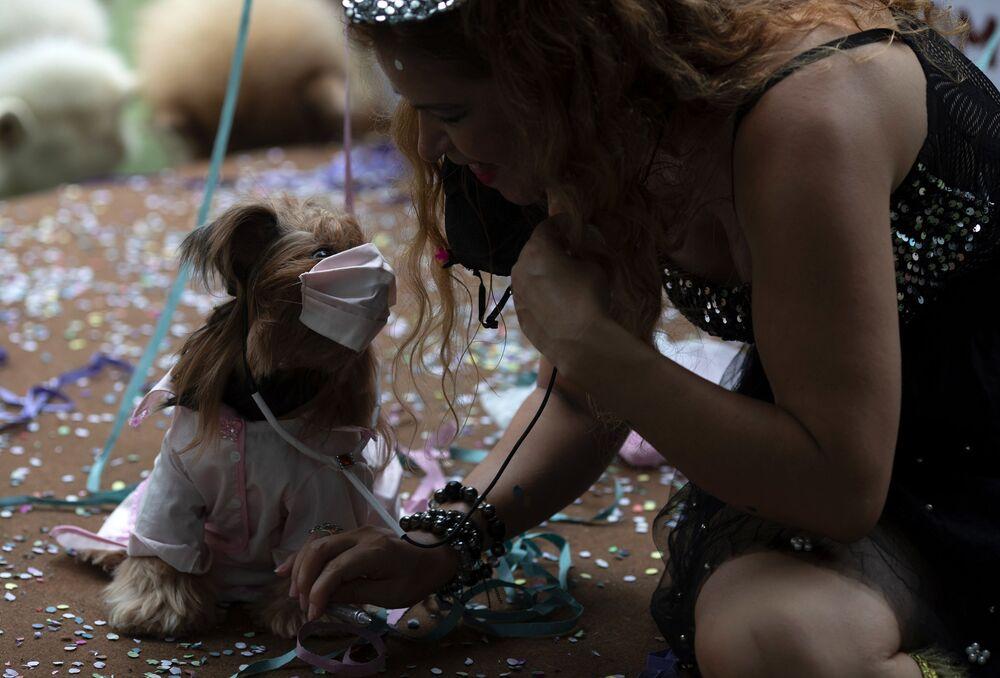 Cachorrinha Eva fantasiada de médica e sua dona em palco coberto de confetes durante o desfile de cachorros anual do Carnaval no Rio de Janeiro, Brasil, 13 de fevereiro de 2021