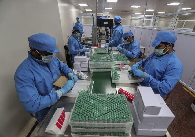Funcionários do Instituto Serum, na Índia, manipulam vacinas contra a COVID-19 desenvolvida pela Universidade de Oxford, em parceria com a farmacêutica AstraZeneca.