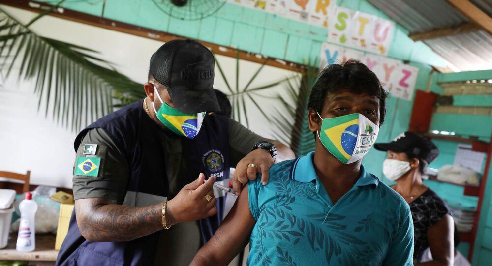Profissional de saúde aplica vacina CoronaVac em indígena da etnia Mura na terra indígena Rio Urubu, no Amazonas