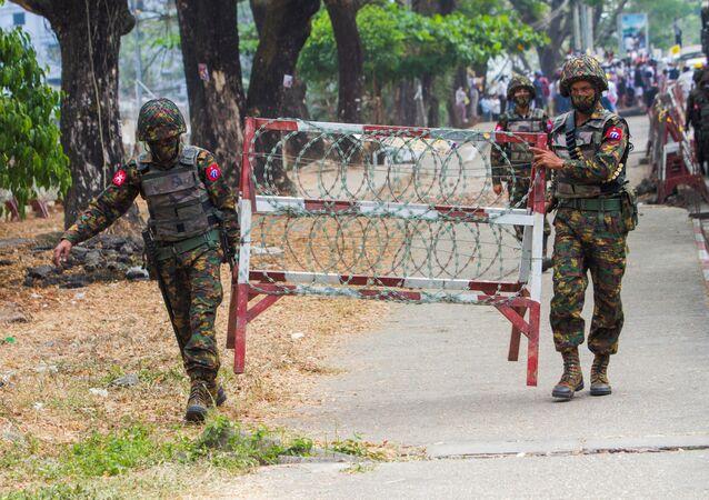 Militares carregam parte de cerca de arame farpado durante protesto contra tomada do poder por militares em Mianmar