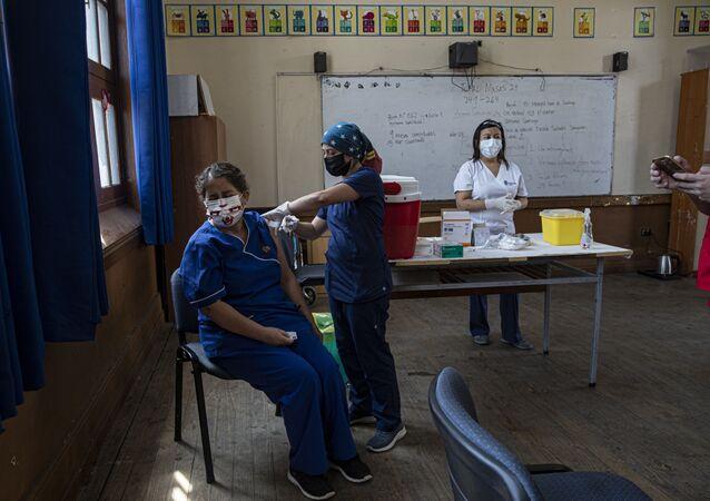 Uma professora é vacinada em um escola na capital Santiago, em 15 de fevereiro de 2021 – o Chile lidera a vacinação na América Latina.