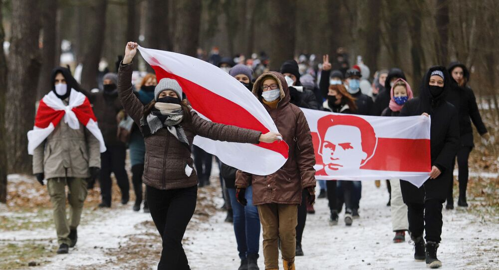 Manifestantes com máscaras faciais carregam antigas bandeiras nacionais da Bielorrússia durante ação de protesto em Minsk, Bielorrússia, 13 de dezembro de 2020