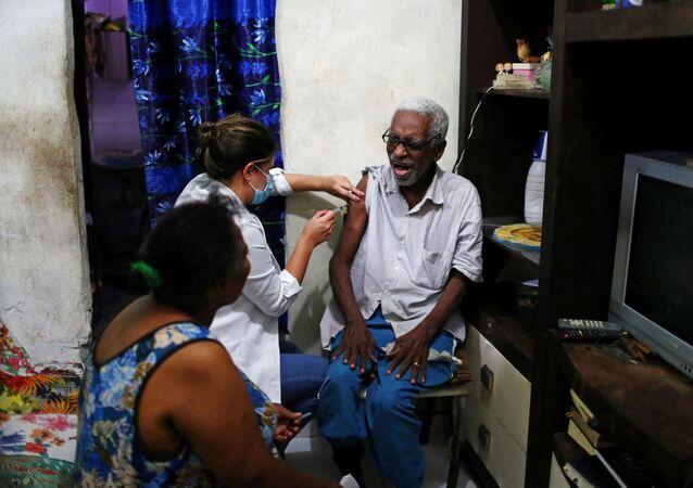 Idoso é vacinado contra o coronavírus no morro do Turano, no Rio de Janeiro