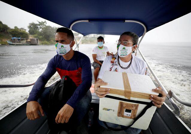 Profissionais de saúde carregam lote de doses da vacina CoronaVac em barco próximo à Terra Indígena Rio Urubu, em Itacoatiara, no Amazonas