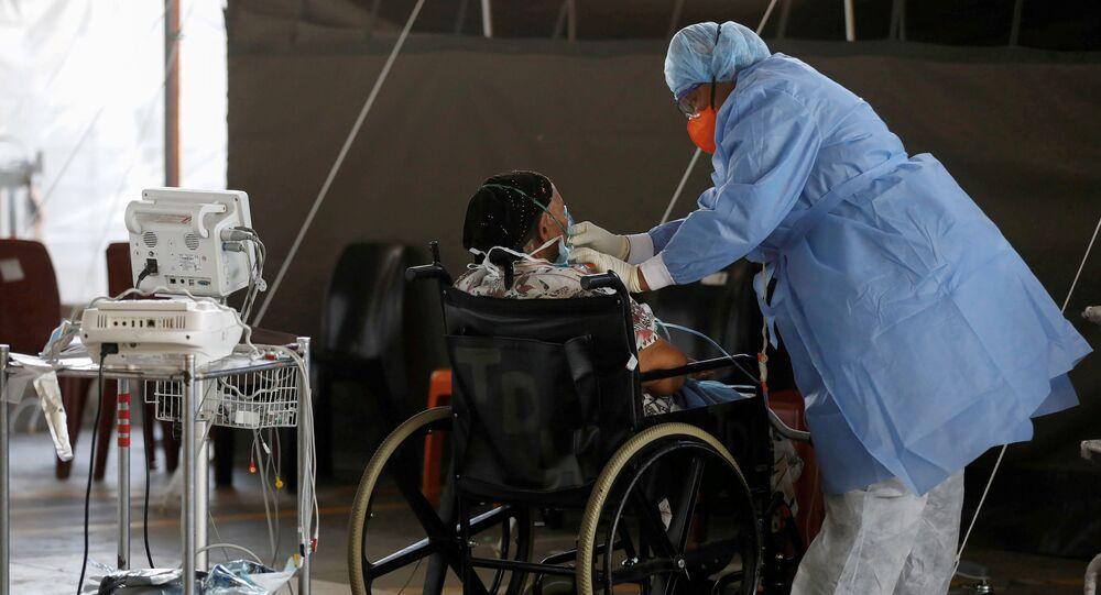 Profissional de saúde atende um paciente em uma enfermaria temporária montada durante o surto da COVID-19, África do Sul, 19 de janeiro de 2021.