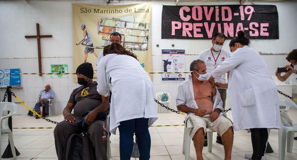 Em São Paulo, agentes de saúde vacinam pessoas idosas em situação de rua contra a COVID-19, no Núcleo de Convivência São Martinho Lima, em 12 de fevereiro de 2021