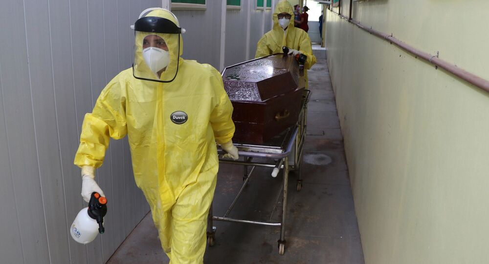 Caixão com o corpo de vítima da COVID-19, é retirado por agentes funerários com a ajuda de familiar de hospital na cidade de  Lábrea, no Amazonas.