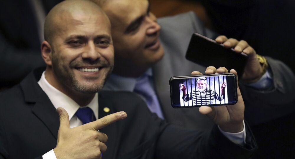 O deputado federal Daniel Silveira (PSL-RJ) segura imagem no celular com uma montagem do ex-presidente Luiz Inácio Lula da Silva preso em sessão da Câmara dos Deputados.