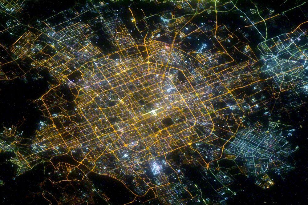 Pequim de noite, China, fotografada por cosmonauta russo a partir da EEI