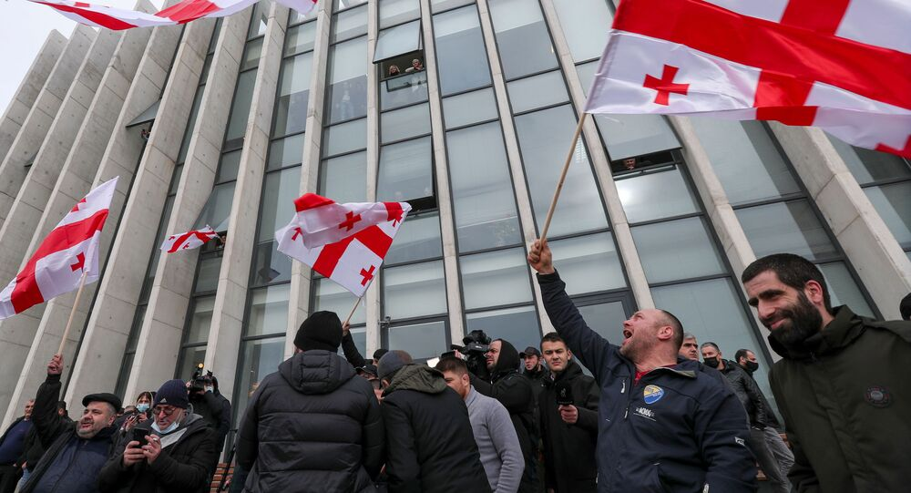 Apoiadores da oposição agitam bandeiras após anúncio da renúncia de Giorgi Gakharia, primeiro-ministro georgiano, fora da sede do partido Movimento Nacional Unido em Tbilisi, Geórgia, 18 de fevereiro de 2021