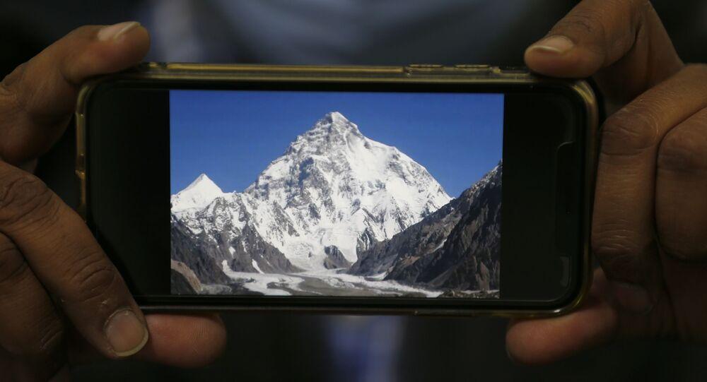 Foto do K2, a segunda montanha mais alta do mundo, na tela de um telefone celular