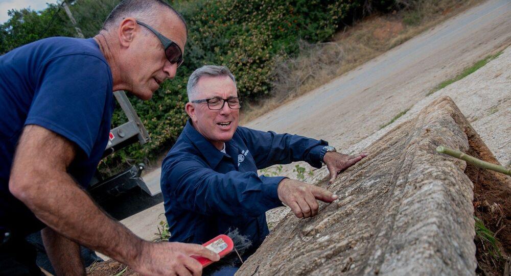 Arqueólogos da IAA limpam e analisam um dos caixões encontrados durante as obras