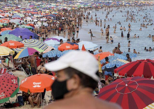 Homem de máscara contra coronavírus na praia do Leblon, no Rio de Janeiro, durante feriado do Carnaval
