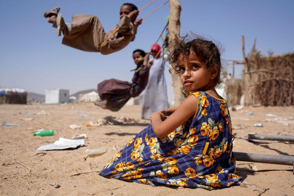 Menina aguarda sua vez perto de balanço no campo de deslocados internos em Marib, Iêmen, 16 de fevereiro de 2021