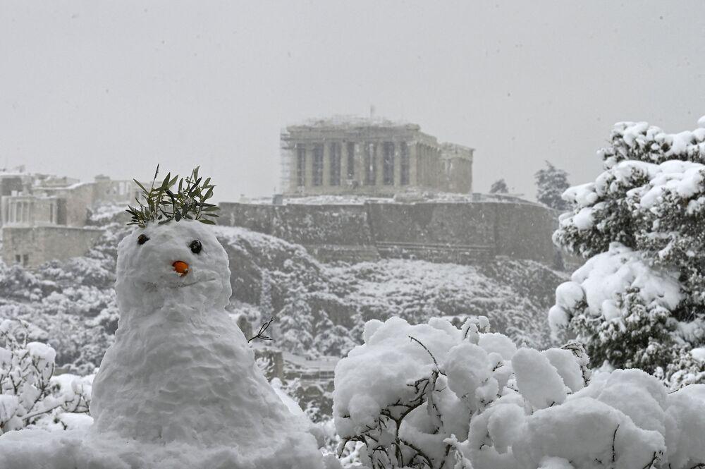Boneco de neve tendo ao fundo a Acrópole em Atenas, Grécia, durante forte nevasca, 16 de fevereiro de 2021
