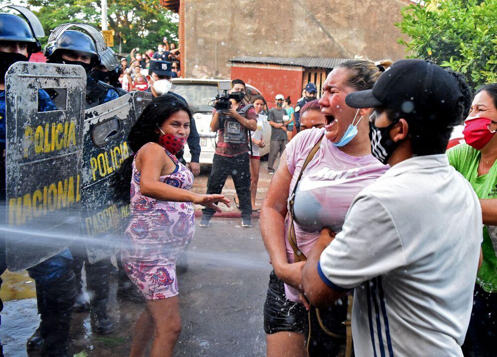 Familiares de detentos na prisão de Tacumbú, Paraguai, são pulverizados com água pela polícia durante confrontos após a morte de seis presos, 16 de fevereiro de 2021