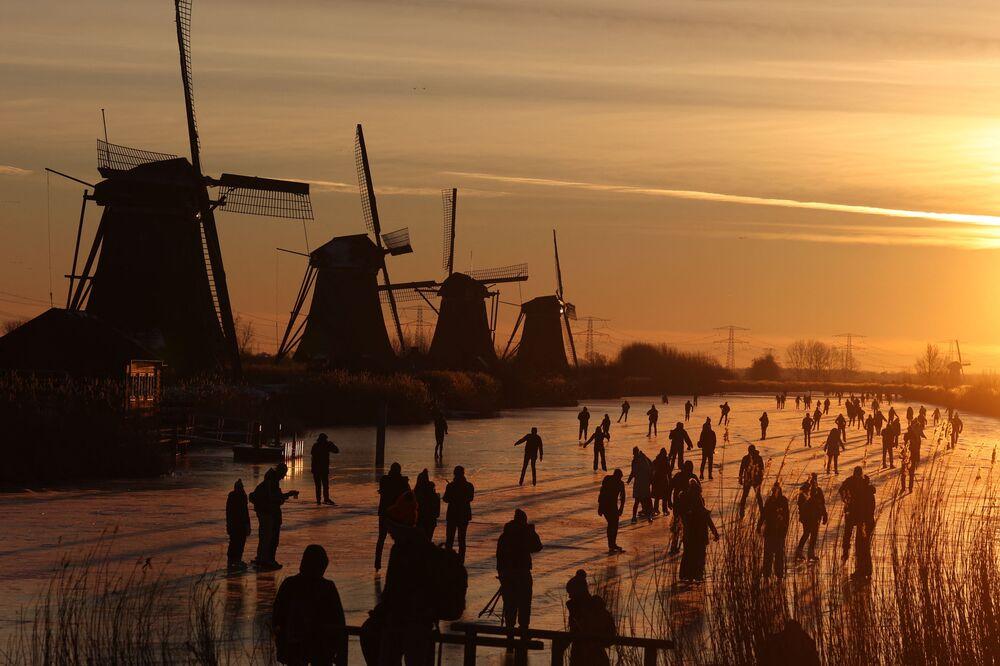 Patinadores deslizam no gelo perto de moinhos de vento no povoado de Kinderdijk, Países Baixos, 14 de fevereiro de 2021