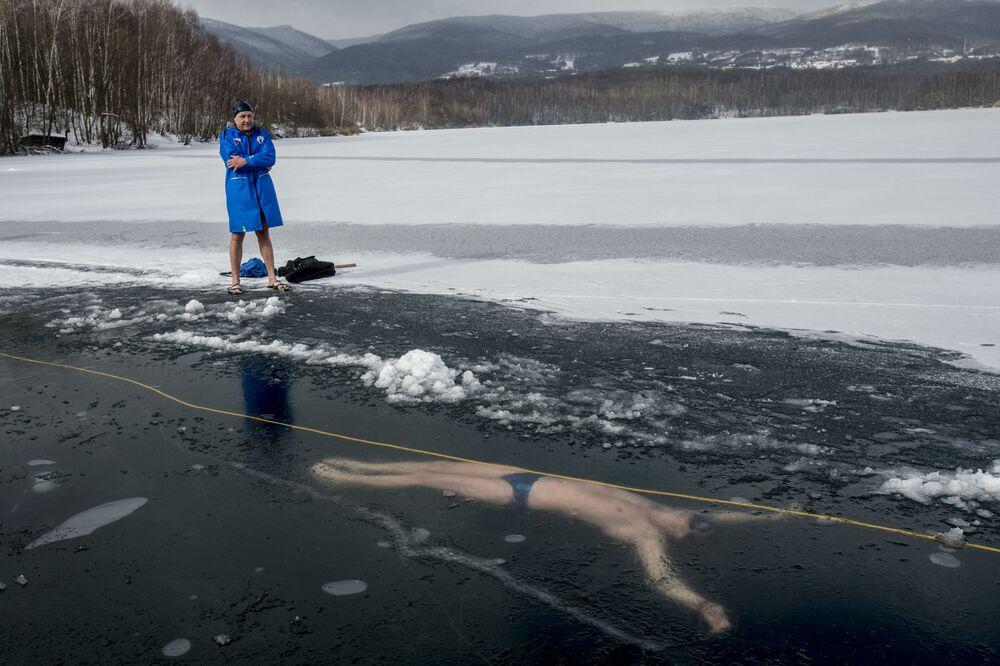 Homem perto do lago Barbora, República Tcheca, onde seu amigo, David Vencl, nada debaixo do gelo durante treinamento para bater o recorde Guinness de mergulho mais longo debaixo do gelo, 13 de fevereiro de 2021