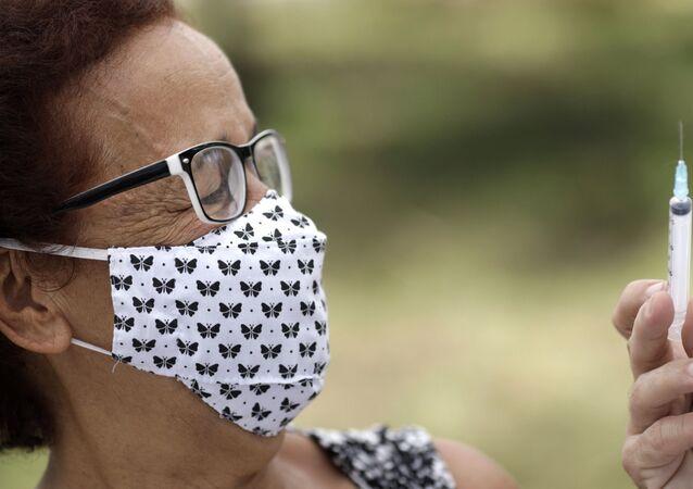 Médico mostra seringa vazia a uma mulher após aplicar a vacina CoronaVac da farmacêutica chinesa Sinovac, São Gonçalo, Rio de Janeiro, 18 de fevereiro de 2021