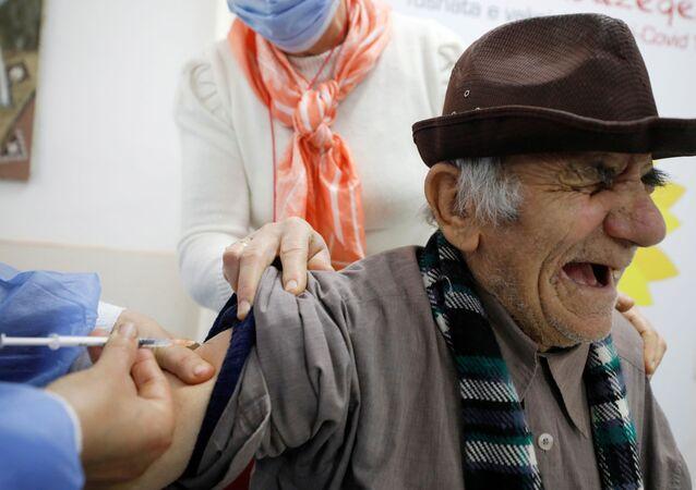 Homem recebe dose da vacina da Pfizer/BioNTech, Fier, Albânia, 19 de fevereiro de 2021