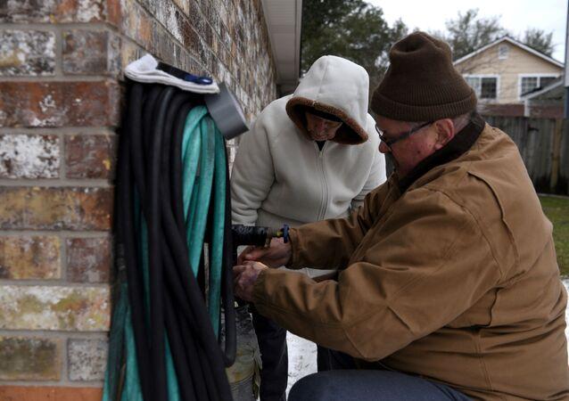 Buddy e Barbara Preston tentam consertar um cano, que congelou, enquanto o estado do Texas experimenta grandes cortes de energia e temperaturas recordes em Houston, EUA, em 16 de fevereiro de 2021