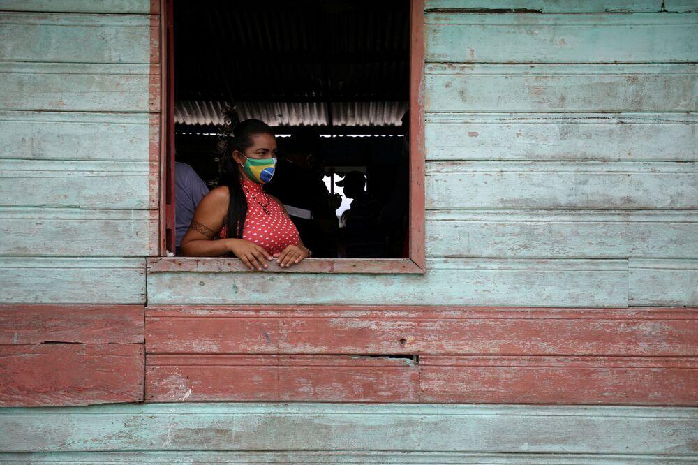 Mulher indígena aguarda para receber a vacina da Sinovac na margem do rio Urubu, no estado de Amazonas, Brasil, 13 de fevereiro de 2021
