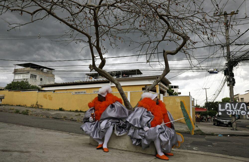 Dois homens de bate-bola sentados em subúrbio do Rio de Janeiro durante tradicionais celebrações do Carnaval no Brasil, apesar de estas terem sido canceladas devido à pandemia do coronavírus, 14 de fevereiro de 2021