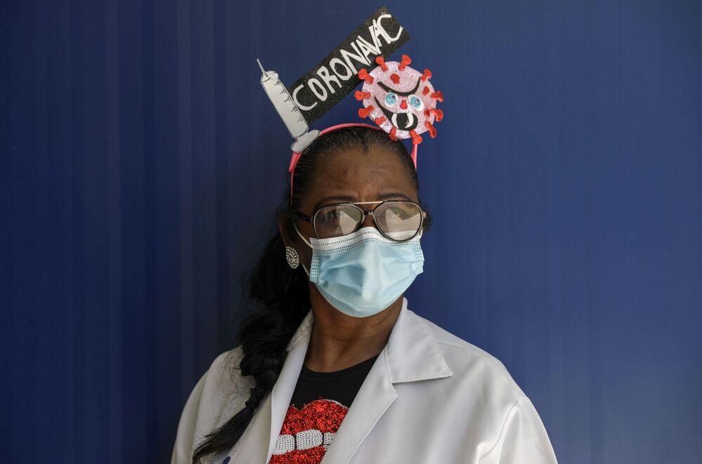 Funcionária da saúde Sonia Mara com ornamento de carnaval em clínica municipal que funciona como estação de vacinação contra COVID-19, enquanto celebrações tradicionais foram canceladas devido à pandemia, Rio de Janeiro, Brasil, 16 de fevereiro de 2021