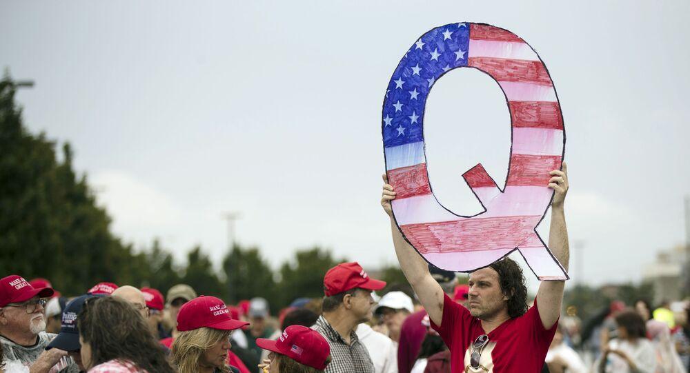 Adepto do movimento QAnon elevando cartaz em forma de Q