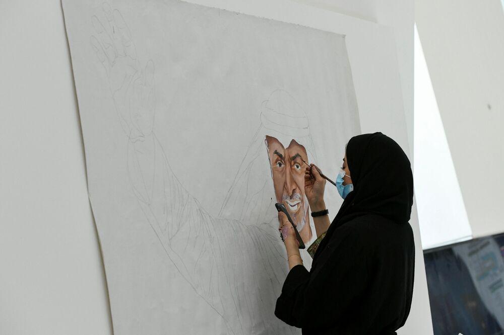 Mulher pinta o retrato do príncipe herdeiro de Abu Dhabi, xeque Mohammed bin Zayed al-Nahyan durante a exposição de defesa IDEX 2021 em Abu Dhabi, EAU, 21 de fevereiro de 2021