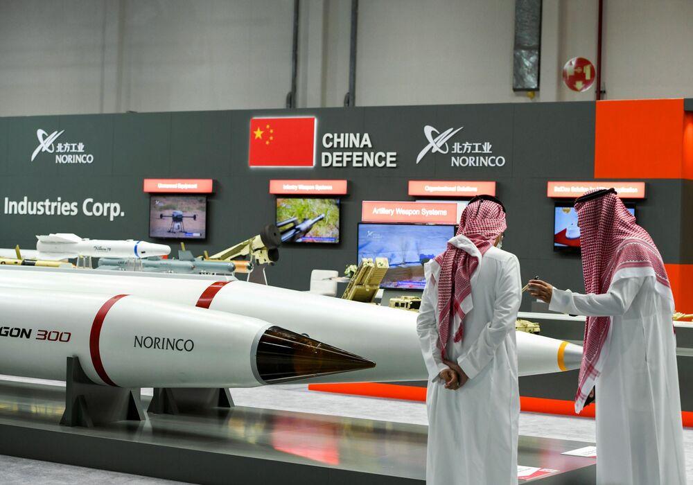 Homens ao lado de produtos em exposição na IDEX 2021 em Abu Dhabi, EAU, 21 de fevereiro de 2021