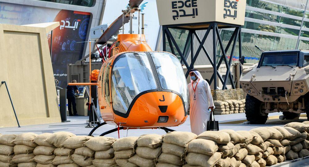 Homem perto de um helicóptero no estande do grupo tecnológico EDGE na exposição de defesa IDEX 2021 em Abu Dhabi, EAU, 22 de fevereiro de 2021