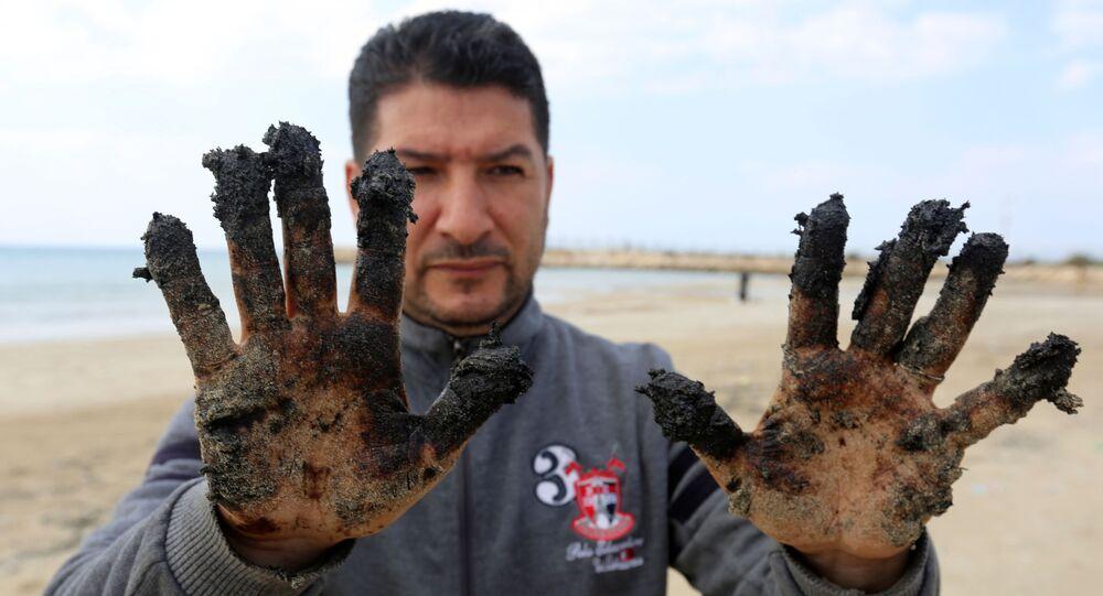 Homem mostra alcatrão nas mãos na sequência de um derramamento que alagou grande parte da costa do Mediterrâneo