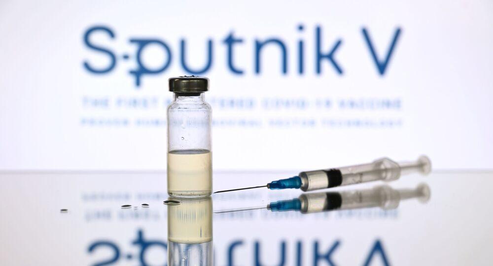 Seringa e ampola com o logotipo da Sputnik V ao fundo