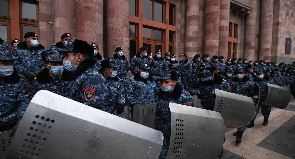 Policiais usam máscaras protetoras durante uma manifestação exigindo a renúncia do primeiro-ministro Nikol Pashinyan, na Praça da República, em Erevan, Armênia