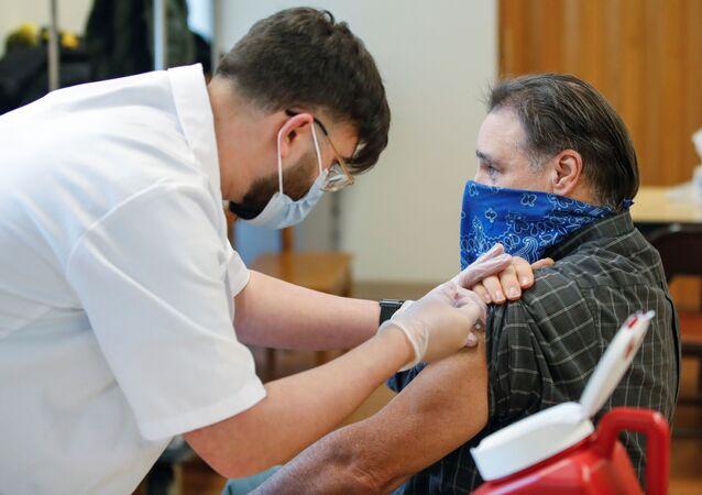 Enfermeiro aplica vacina da Pfizer em homem na cidade de Evanston, no estado de Illinois, nos EUA