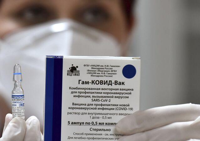 Em Pogdorica, capital de Montenegro, um profissional de saúde segura uma dose da vacina russa contra a COVID-19, Sputnik V, em 23 de fevereiro de 2021