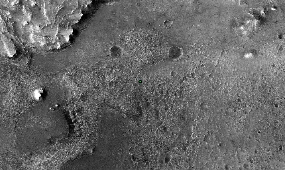 Um ponto verde marca o lugar de pouso do rover Perseverance da NASA na cratera Jezero, imagem feita pela câmera de Experimento de Ciência em Imagem de Alta Resolução (HiRISE, na sigla em inglês), 18 de fevereiro de 2021