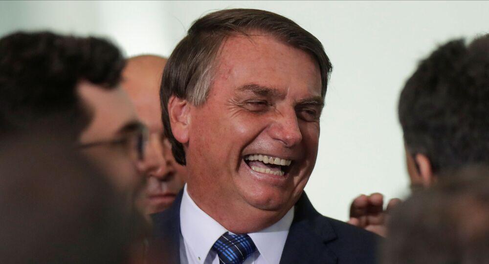 Presidente do Brasil, Jair Bolsonaro, ri durante cerimônia com prefeitos no Palácio do Planalto, em Brasília, 23 de fevereiro de 2021