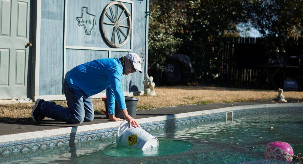 Morador do Texas coleta água de sua piscina, em meio à falta de água e energia no estado norte-americano do Texas, 20 de fevereiro de 2021