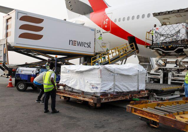 Empregados descarregam caixas com a vacina da AstraZeneca/Oxford, com o país recebendo seu primeiro lote de vacinas da aliança COVAX, Aeroporto Internacional de Acra, Gana, 24 de fevereiro de 2021