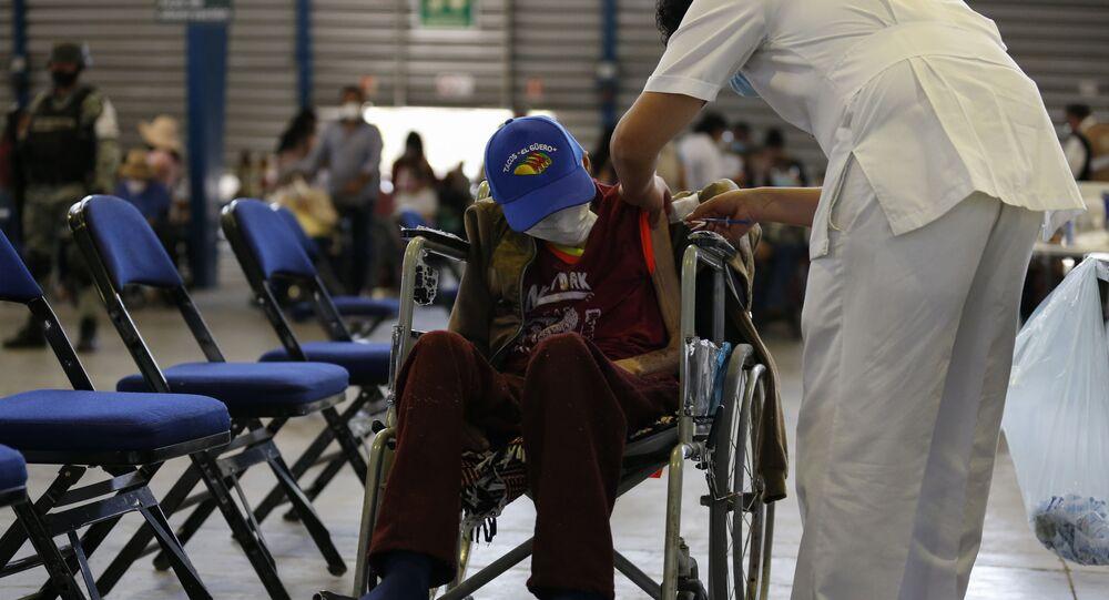 Na Cidade do México, um profissional de saúde aplica uma dose da vacina Sputnik V contra a COVID-19 em um idoso, no Palacio de Los Deportes, em 24 de fevereiro de 2021