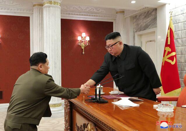 Líder norte-coreano, Kim Jong-un, cumprimenta servidor durante 8ª Reunião da Comissão Militar Central do país, em Pyongyang, Coreia do Norte, 24 de fevereiro de 2021