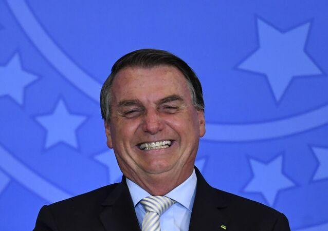Jair Bolsonaro sorri em foto tirada no Palácio do Planalto.